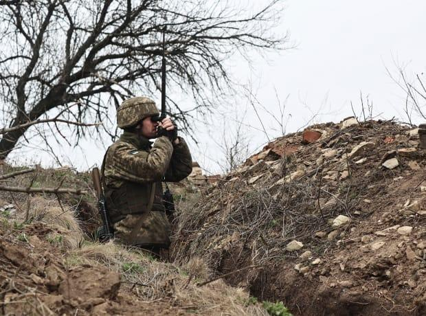 A Ukrainian soldier looks through a periscope at fighting positions on the line of separation from pro-Russia rebels near Donetsk, Ukraine, on Monday. Ukraine and the West have become increasingly worried about the presence of more Russian troops near the Ukraine-Russia border and urged Moscow to pull them back.  (The Associated Press - image credit)
