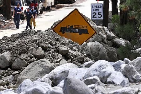 A fire station sign is pictured on a road covered by mud and boulders from a mudflow triggered by flash floods in the San Bernardino National Forest community of Forest Falls, California August 4, 2014. REUTERS/Jonathan Alcorn