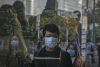 Commuters wearing face masks to help curb the spread of the coronavirus are reflected on a window panel as they walk out from a subway station during the morning rush hour in Beijing, Monday, Oct. 19, 2020. (AP Photo/Andy Wong)