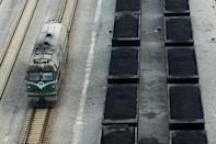 Freight cars (right) filled with coal parked inside a coal mining facility in Huaibei, in northern China's Anhui province on March 5, 2014