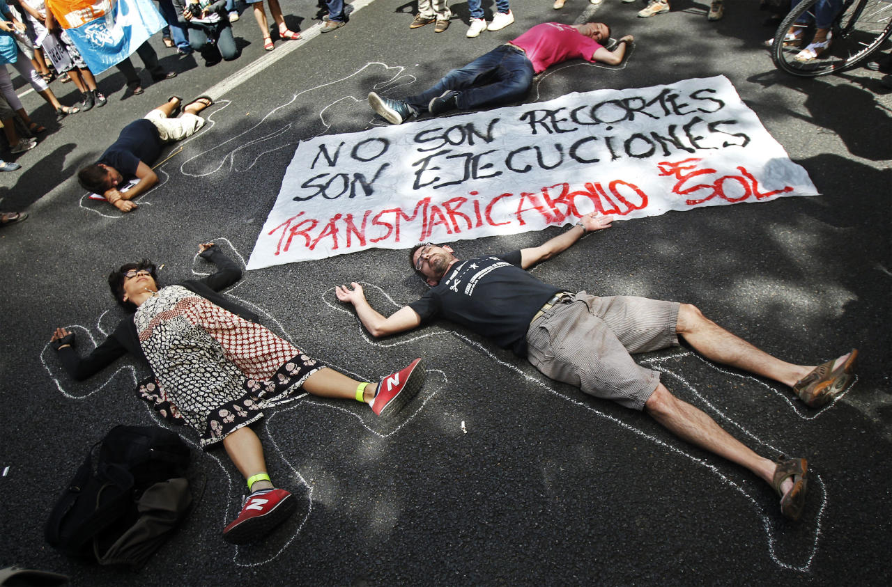 "People perform showing a banner reading ""they are not financial cuts but executions"", against healthcare austerity measures announced by the Spanish government in Madrid, Spain, Saturday, Sept. 1, 2012. Some 300 people have blocked a ring road in Madrid to protest the introduction of spending cuts that will leave more than 150,000 non-registered immigrants without healthcare in Spain. Illegal immigrants who do not contribute taxes to social security are, as of Saturday, to lose national health cards that had entitled them to free treatment in case of illness. (AP Photo/Andres Kudacki)"