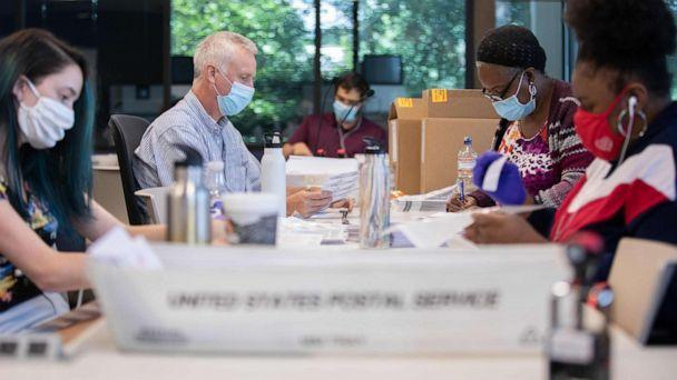 PHOTO: Absentee ballot election workers stuff ballot applications at the Mecklenburg County Board of Elections office in Charlotte, North Carolina, Sept. 4, 2020. (Logan Cyrus/AFP via Getty Images)