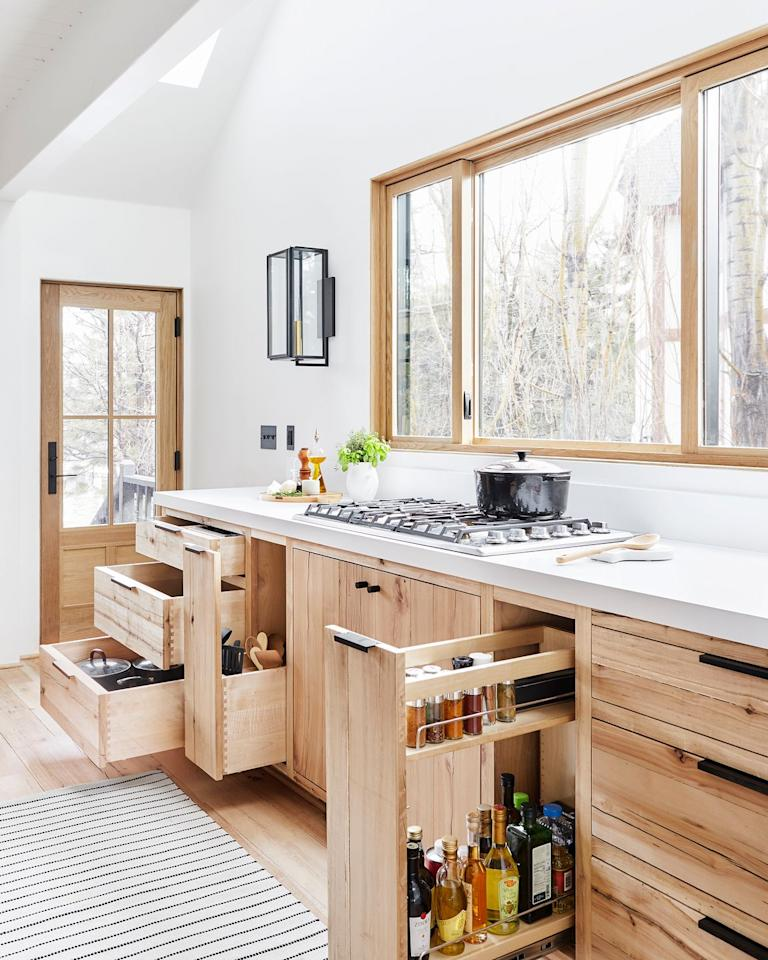 """<p>In this kitchen designed by <a href=""""https://stylebyemilyhenderson.com/"""" target=""""_blank"""">Emily Henderson</a>, spices, dry goods, and other cooking essentials are stored in a pull-out """"pantry."""" This keeps then tucked away but still provides easy access. Organize each one by item type. </p>"""