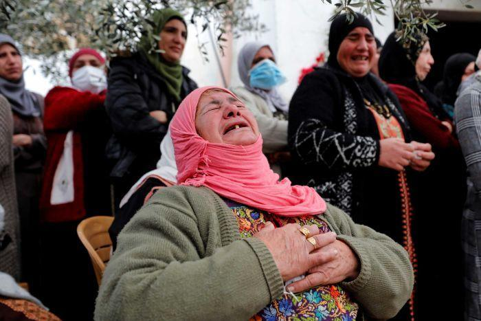 A woman in a pink headscarf grips her chest and sobs at a funeral