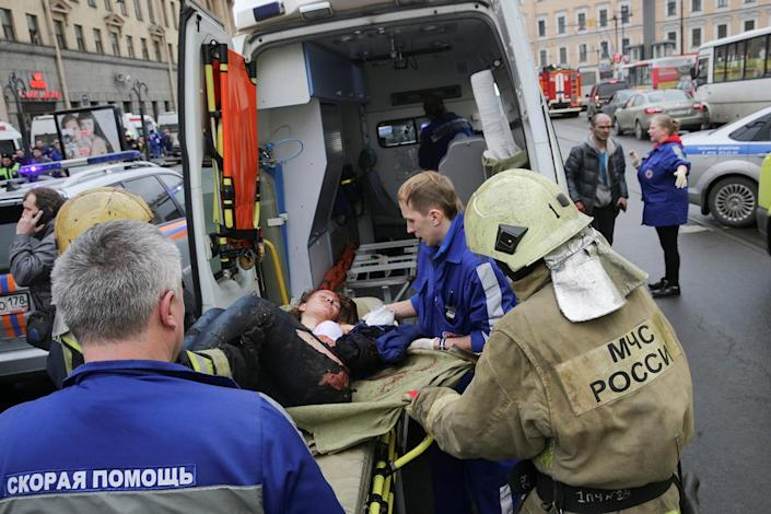 <p>An injured person is helped by emergency services personnel outside Sennaya Ploshchad metro station in St. Petersburg, Russia, April 3, 2017. (Anton Vaganov/Reuters) </p>