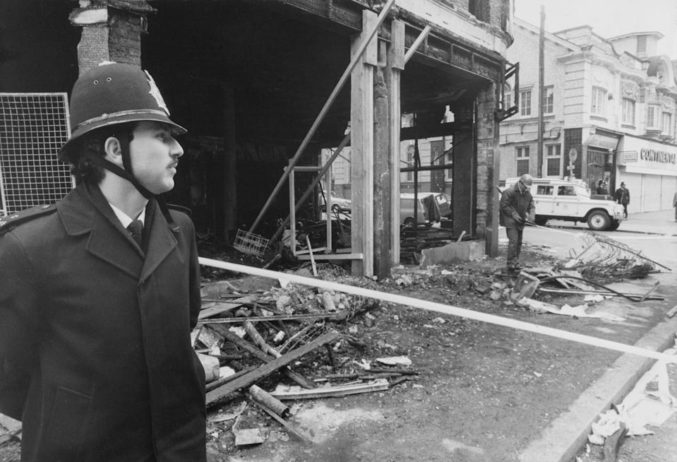 A police officer stands next to a gutted building on Coldharbour Lane after riots erupted on the streets of Brixton in April 1981Getty Images