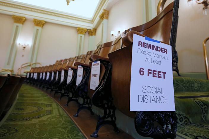 Signs posted in the Assembly gallery remind visitors to stay 6 feet apart, at the Capitol in Sacramento, Calif., in May.