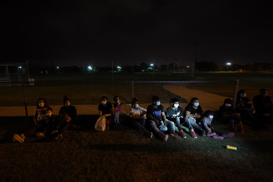 Migrants wait at an intake area after turning themselves in upon crossing the U.S.-Mexico border, late Tuesday, May 11, 2021, in La Joya, Texas. The U.S. government continues to report large numbers of migrants crossing the U.S.-Mexico border with an increase in adult crossers. But families and unaccompanied children are still arriving in dramatic numbers despite the weather changing in the Rio Grande Valley registering hotter days and nights. (AP Photo/Gregory Bull)
