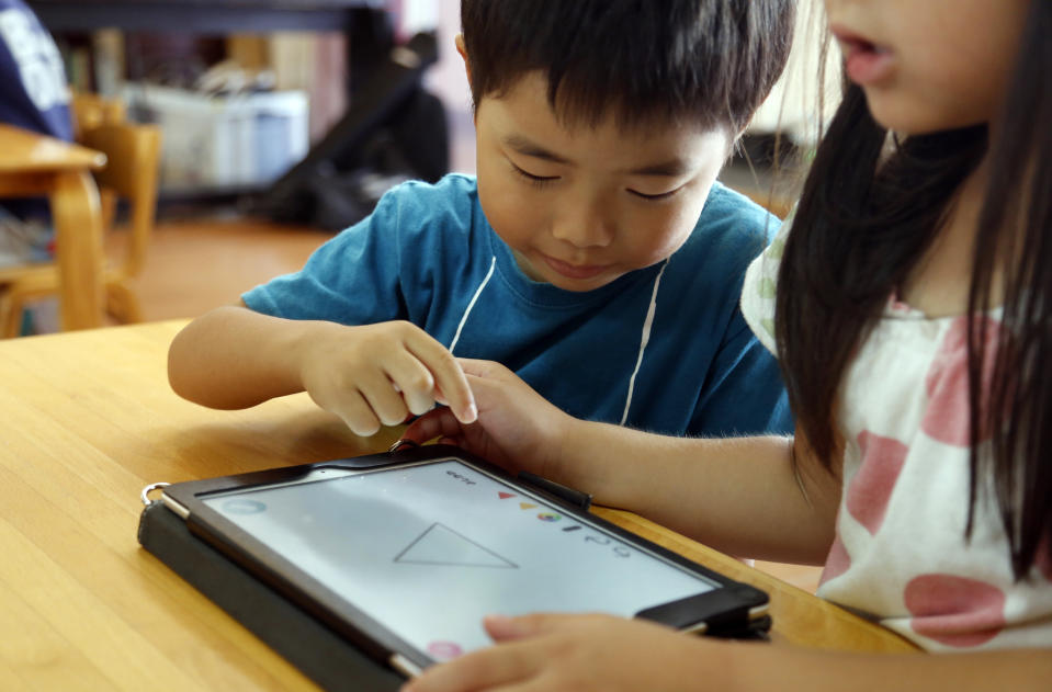 Data reveals that moms are much more generous with allowing their children to use electronics during the pandemic. (AP Photo/Yuri Kageyama)