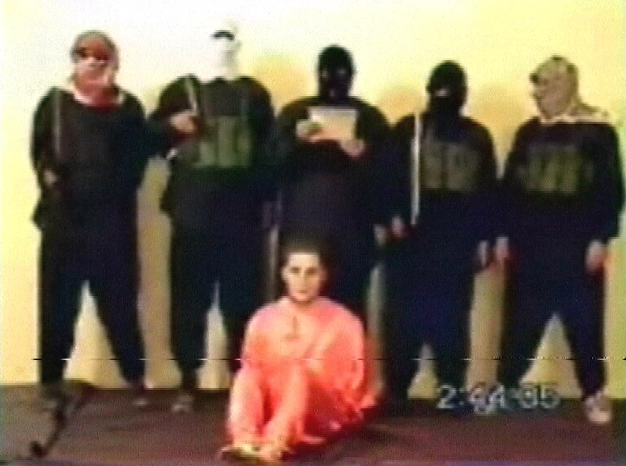 """A frame grab taken from website video footage May 11, 2004, shows a man, who identified himself as Nick Berg of Philadelphia (C) seated in front of his five masked captors moments before he was executed. Al Qaeda's leader in Iraq beheaded an American civilian and vowed more killings in revenge for the abuse of Iraqi prisoners, an Islamist Web site said on Tuesday.  After one of the masked men read out a statement, they pushed Berg to the floor and shouted """"God is greatest"""" above his screams as one of them sawed his head off with a large knife then held it aloft for the camera.   It was not immediately possible to verify the authenticity of the tape carried on the Muntada al-Ansar Islamist Web site."""