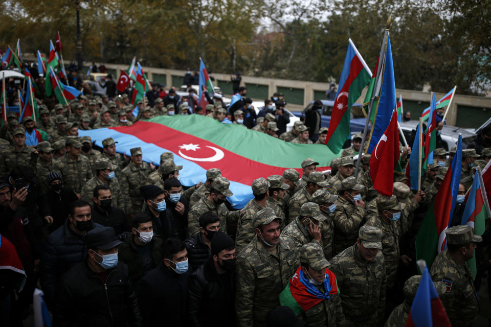 Azerbaijani soldiers carry a huge national flag as they celebrate the transfer of the Lachin region to Azerbaijan's control, as part of a peace deal that required Armenian forces to cede the Azerbaijani territories they held outside Nagorno-Karabakh, in Aghjabadi, Azerbaijan, Tuesday, Dec. 1, 2020. Azerbaijan has completed the return of territory ceded by Armenia under a Russia-brokered peace deal that ended six weeks of fierce fighting over Nagorno-Karabakh. Azerbaijani President Ilham Aliyev hailed the restoration of control over the Lachin region and other territories as a historic achievement. (AP Photo/Emrah Gurel)