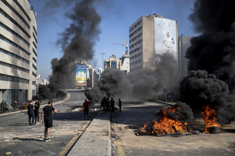 Protesters stand next to burning tires set on fire to block a main road, after the Lebanese pound hit a record low against the dollar on the black market, in Beirut, Lebanon, Saturday, March 6, 2021. (AP Photo/Hassan Ammar)