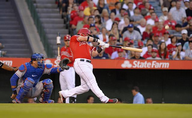 Los Angeles Angels' Kole Calhoun, right, hits a solo home run as Texas Rangers catcher A.J. Pierzynski catches during the first inning of their baseball game, Tuesday, Aug. 6, 2013, in Anaheim, Calif. (AP Photo/Mark J. Terrill)
