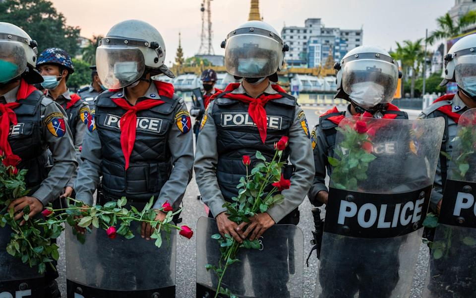 Riot police in Myanmar stand guard with roses given to them by protesters