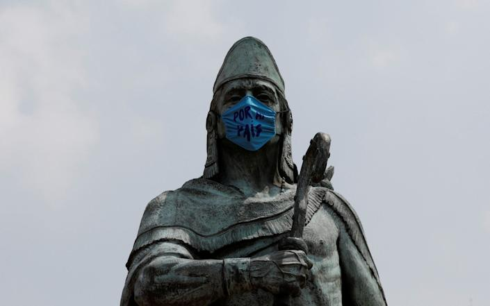 The monument of Tezozomoc is seen with a face mask that reads 'For My Country' in Mexico City - Reuters