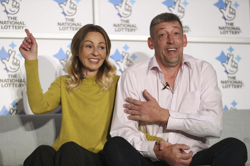 Self-employed builder Steve Thomson and his wife Lenka celebrate their 105 million pounds EuroMillions win (US dollars 135 million) as they face the media at Walberton, England, Tuesday Nov. 26, 2019. Steve and Lenka, who is originally from Slovakia, have three school aged children and have won the 9th largest jackpot ever in the UK. (Andrew Matthews/PA via AP)