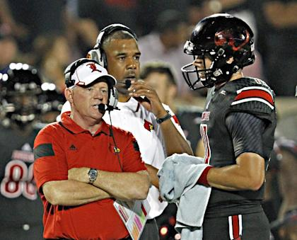 Bobby Petrino (L) talks with quarterback Will Gardner during a timeout. (AP)