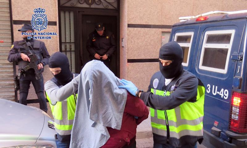 Masked Spanish police officers take an arrested person from an undisclosed location for suspected links to Al-Qaeda and the Islamic State on February 7, 2016