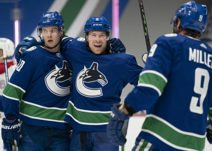 Vancouver Canucks right wing Brock Boeser (6) celebrates his goal against the Montreal Canadiens with Elias Pettersson (40) and J.T. Miller (9) during the second period of an NHL hockey game Wednesday, Jan. 20, 2021, in Vancouver, British Columbia. (Jonathan Hayward/The Canadian Press via AP)