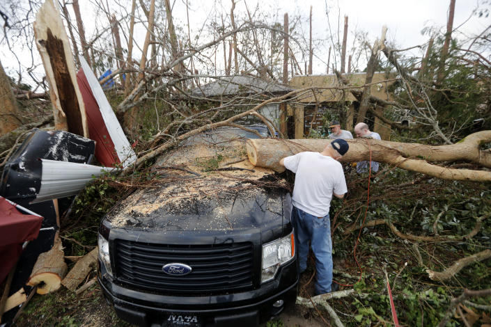 <p>People cut away a tree that'll on a vehicle in the aftermath of Hurricane Michael in Panama City, Fla., Thursday, Oct. 11, 2018. (Photo: Gerald Herbert/AP) </p>