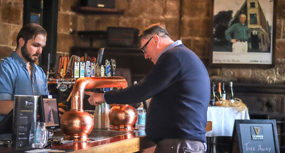 A barman pours a customer a bottle of beer to take away at the Hero of Waterloo pub in The Rocks. Source: Getty