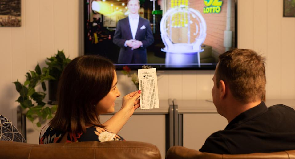 A stock image of a couple sitting on a couch watching an Oz Lotto draw.