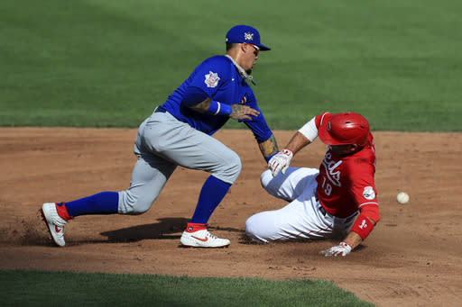 Chicago Cubs' Javier Baez, left, attempts to field the ball as Cincinnati Reds' Joey Votto, right, slides into second base after hitting a double in the third inning during a baseball game at Cincinnati, Saturday, Aug. 29, 2020. (AP Photo/Aaron Doster)