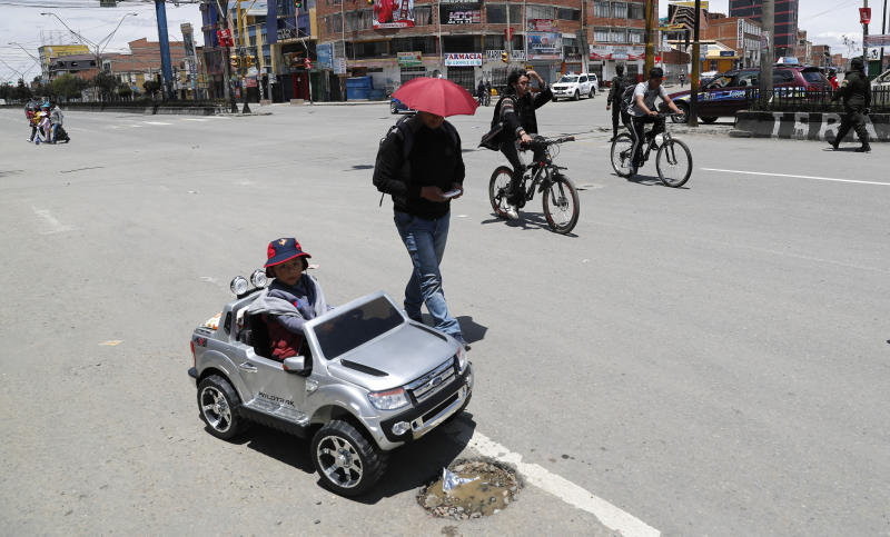 A children sits on a toy car in El Alto, outskirts of La Paz, Bolivia, Sunday, Oct. 20, 2019. Bolivians are voting in general elections Sunday where President Evo Morales is candidate for a fourth term. (AP Photo/Jorge Saenz)