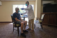Registered Pharmacist Ken Ramey, right, takes the temperature of William M. Derrick, 77, before administering the COVID-19 vaccine, Thursday, Jan. 21, 2021, at the Isles of Vero Beach assisted and independent senior living community in Vero Beach, Fla. (AP Photo/Wilfredo Lee)