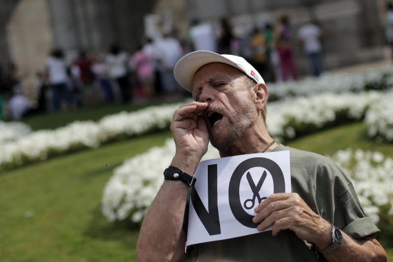 "A protestor shouts slogans as he holds a banner reading ""no financial cuts"" during a demonstration against government-imposed austerity measures and labor reforms in the public healthcare sector in Madrid, Spain, Sunday, July 21, 2013. Madrid residents and medical workers angered by budget cuts and plans to part privatize their cherished national health service protested on the streets Sunday. (AP Photo/Andres Kudacki)"