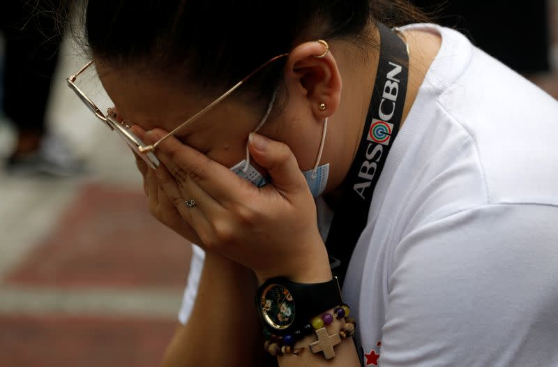 An ABS-CBN employee cries after the Philippine congress voted against the renewal of the broadcast network's 25-year franchise, outside ABS-CBN headquarters, in Quezon City