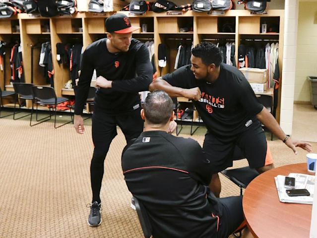 San Francisco Giants outfielder Hunter Pence, left, greets pitcher Jean Machi, right, as catcher Guillermo Quiroz watches in the locker room at baseball spring training, Friday, Feb. 14, 2014, in Scottsdale, Ariz. Giants pitchers and catchers arrived Friday for physicals before beginning training Saturday. (AP Photo/Gregory Bull)