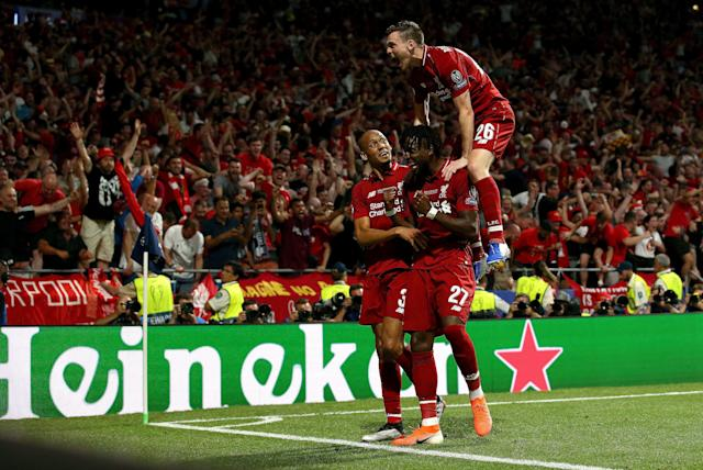 Divock Origi of Liverpool celebrates with teammates Fabinho and Andy Robertson (Photo by Jan Kruger - UEFA/UEFA via Getty Images)