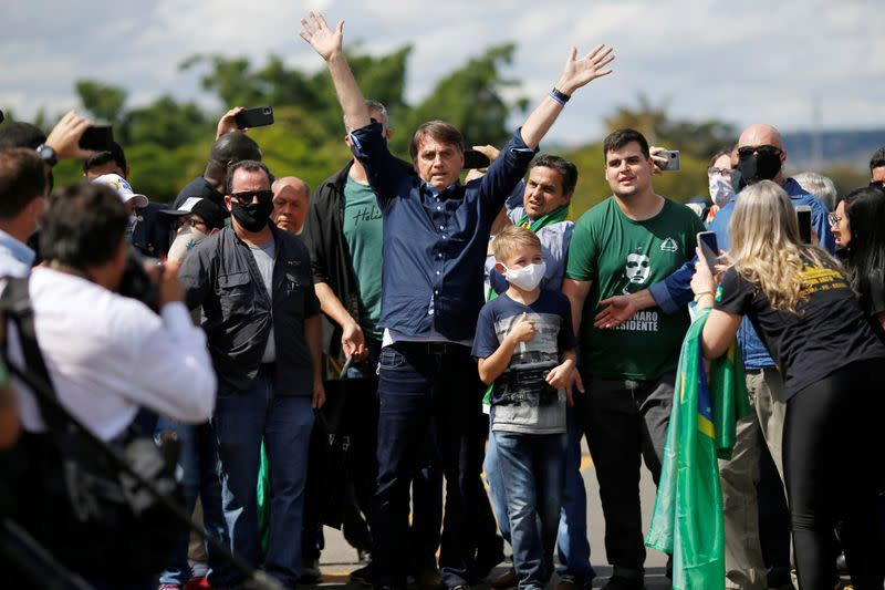 Brazil's President Jair Bolsonaro reacts during a meeting with supporters protesting in his favor in front of the Planalto Palace, amid the coronavirus disease (COVID-19) outbreak, in Brasilia