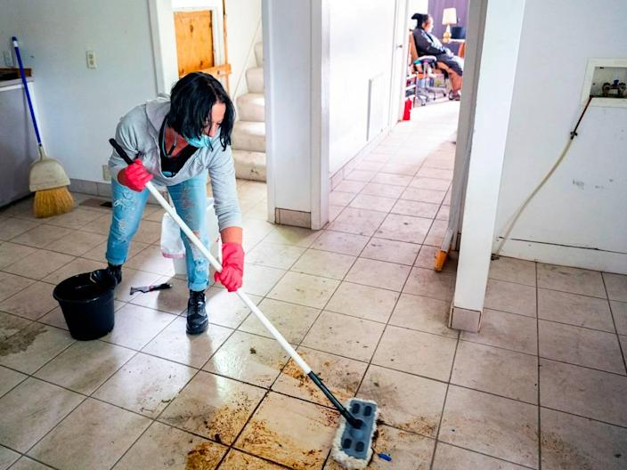 On Thursday afternoon, Amber Haning scrubs the kitchen floor in the home of Helen Wong as a group of kind-hearted volunteers work on deep cleaning the home that was left destitute by a group of squatters in Lewiston. The squatters took advantage of Wong's long absence after she got stuck in Hong Kong while visiting family. She could not travel back to her home in Lewiston because of the COVID-19 global pandemic travel restrictions.