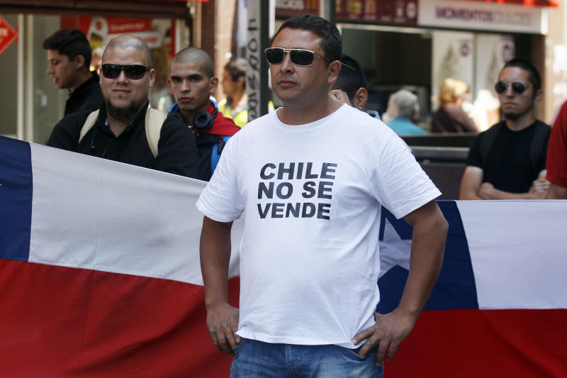 "A Chilean nationalists with a t-shirt that reads in Spanish, ""Chile is not for Sale"", shows his displeasure at the recent world court ruling in Santiago, Chile, Jan. 27, 2014. The United Nations' highest court set a maritime boundary between Chile and Peru, granting the latter a bigger piece of the Pacific Ocean but keeping rich coastal fishing grounds in Chilean hands. (AP Photo/ Luis Hidalgo)."