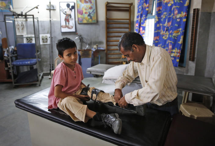 An Indian man puts on an orthoses on his polio-affected boy Manish, 8, at a physical rehabilitation center in New Delhi, India Thursday, March 27, 2014. The World Health Organization has formally declared India polio-free, with no new case of the disease detected in the country in the past three years. (AP Photo /Manish Swarup)