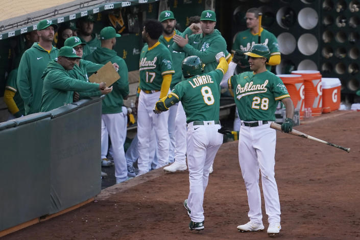 Oakland Athletics' Jed Lowrie (8) is congratulated by teammates, including Matt Olson (28), after hitting a home run against the Kansas City Royals during the fourth inning of a baseball game in Oakland, Calif., Thursday, June 10, 2021. (AP Photo/Jeff Chiu)