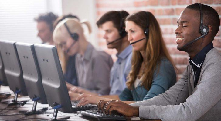 Five young customer support specialists sit in a row at computers with headsets on.