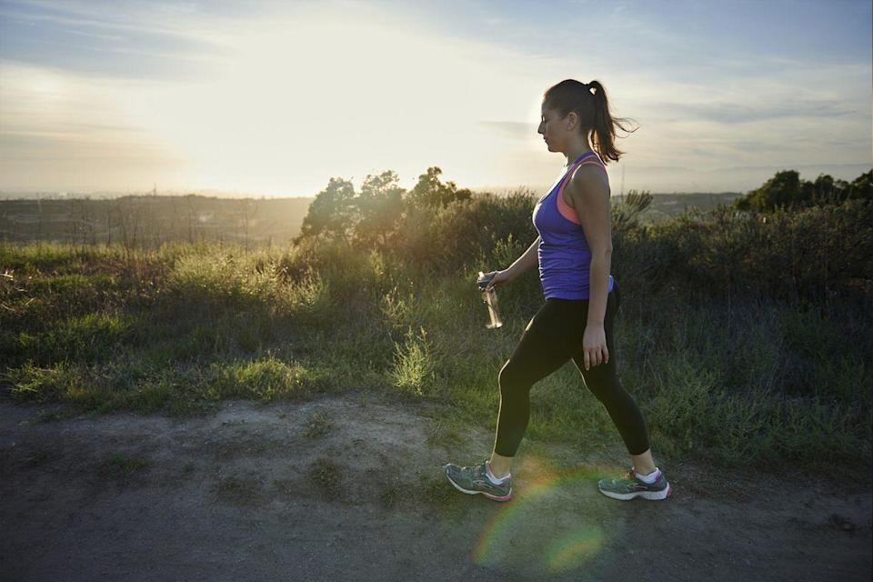"""<p><a href=""""https://www.womansday.com/health-fitness/a33342262/mindful-walking-what-is-it/"""" rel=""""nofollow noopener"""" target=""""_blank"""" data-ylk=""""slk:Mindful walking"""" class=""""link rapid-noclick-resp"""">Mindful walking</a> is good for your mind and helps pass the time. Try this 10-minute walking meditation from the experts at mindful.org: </p><p> Begin your walk at a natural place, holding your arms in a comfortable position. Pay attention to the lift and fall of your foot with each step. Notice how your legs stride and how your body shifts from side to side. If your attention wanders, shift it back to your body sensations — this first step is all about you.</p><p>After a few minutes, turn your attention to the sounds around you. Do you hear birds chirping? A lawnmower whirring? Take in every sound, both pleasant and unpleasant.</p><p>Now shift your awareness to smell. Perhaps you get a whiff of car exhaust or the gentle scent of fresh cut grass. Breathe it all in.</p><p> Move on to vision. Take in the colors, objects, and scenery all around you. Maybe you notice your neighbor planted a new flowerbed out front, or you realize the trees are finally in bloom.</p><p> In the last few minutes, bring your awareness back from your surroundings to your body sensation.</p>"""