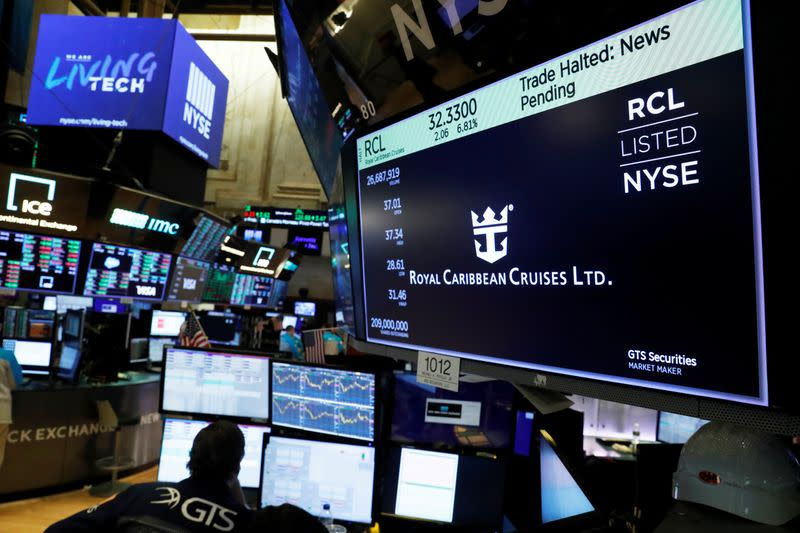 Traders wait for stocks to resume trading on Royal Caribbean Cruises Ltd. on the floor of the New York Stock Exchange in New York