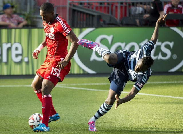 Toronto FC defender Doneil Henry, left, battles for the ball against Sporting Kansas City forward C.J. Sapong during the first half of an MLS soccer game Saturday, July 26, 2014, in Toronto. (AP Photo/The Canadian Press, Nathan Denette)