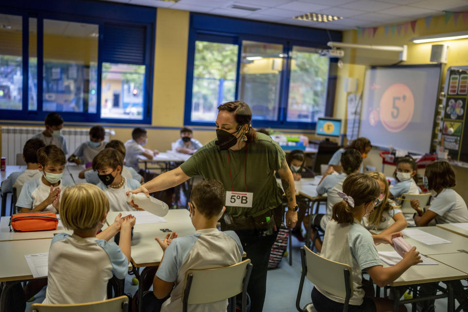 A teacher wearing a face mask to protect against the spread of coronavirus administers a disinfectant gel to a pupil at Maestro Padilla school as the new school year begins, in Madrid, Spain, Tuesday, Sept. 7, 2021. Around 8 million children in Spain are set to start the new school year. (AP Photo/Manu Fernandez)