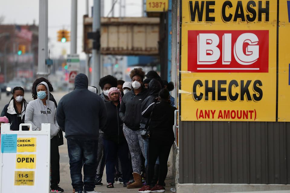 People wear face masks waiting outside a beauty salon and check cashing facility as the coronavirus disease (COVID-19) continues to spread, in the Highland Park section of Detroit, Michigan U.S., April 25, 2020.  REUTERS/Shannon Stapleton