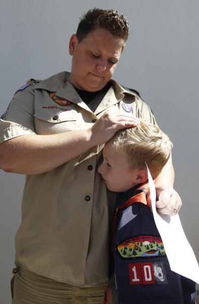 FILE - In this July 18, 2012 file photo, Jennifer Tyrrell hugs her son Cruz Burns, 7, outside Boy Scouts national offices in Irving, Texas, after a meeting with representatives of the 102-year-old organization. The Ohio woman was ousted as a den mother because she is a lesbian. The Boys Scouts of America announced Monday, Jan. 28, 2013, that it is considering a dramatic retreat from its controversial policy of excluding gays as leaders and youth members. (AP Photo/LM Otero, File)