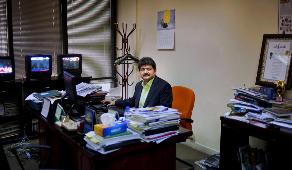 FILE - In this March 14, 2017, file, photo, Pakistani journalist Hamid Mir sits in his office in Islamabad, Pakistan. A Pakistani television station on Monday, May 31, 2021, took Mir off air, removing him as host of a popular talk show after he criticized the country's powerful military. (AP Photo/Anjum Naveed, File)