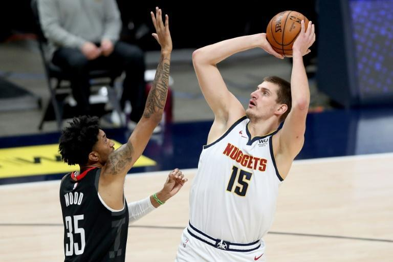 Denver's Nikola Jokic shoots over Houston's Christian Wood on the way to a triple-double in the Nuggets' 124-111 NBA victory over the Rockets