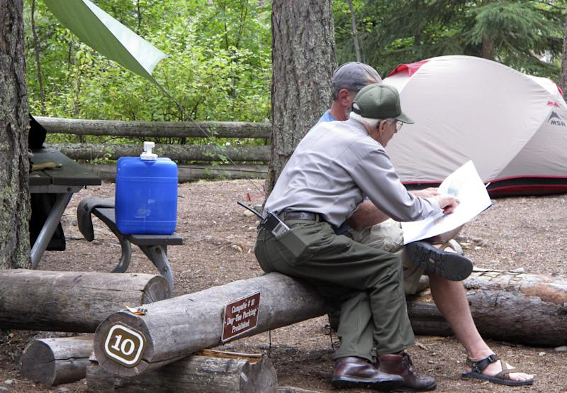 This Sept. 5, 2013 photo shows Lyle Ruterbories pointing out routes on a map with a visitor to the Kintla Lake Campground in Glacier National Park, Mont. Ruterbories is the National Park Service's oldest ranger at age 93. He and his wife Marge managed the campground since 1991, and Ruterbories has continued on his own since she died in 2005. (AP Photo/Matt Volz)