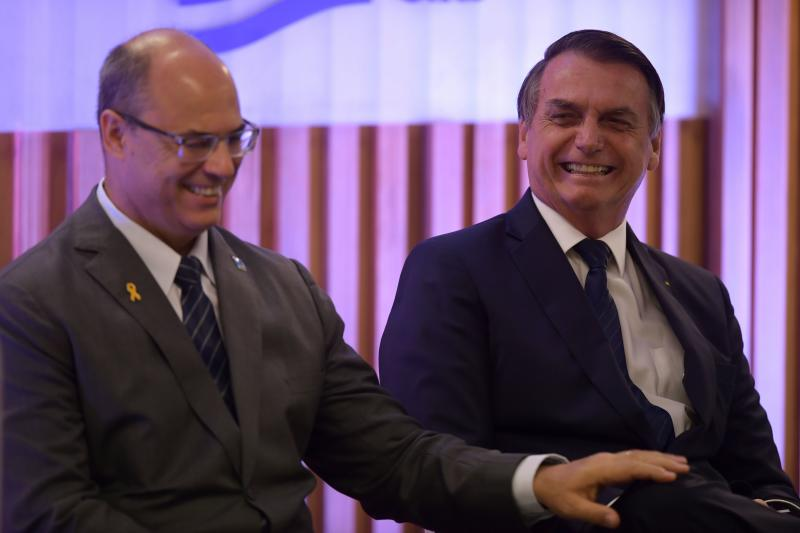 Rio de Janeiro's Governor Wilson Witzel (L) and Brazilian President Jair Bolsonaro attend a ceremony at the Federation of Industries of Rio de Janeiro (FIRJAN) headquarters in Rio de Janeiro on May 20, 2019. (Photo by MAURO PIMENTEL / AFP) (Photo credit should read MAURO PIMENTEL/AFP via Getty Images)