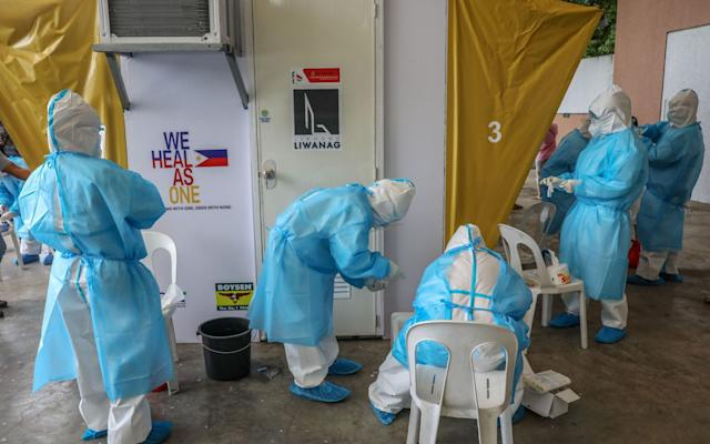 Health workers prepare equipment for swabbing at a testing facility in Quezon City, northeast of Manila, Philippines, 30 July 2020. - Mark R Cristino/EPA-EFE/Shutterstock